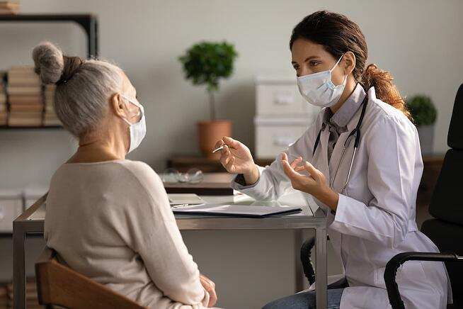 Doctor wearing a mask while taking to patient wearing a mask