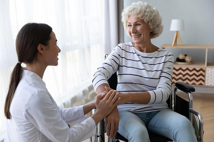 Physician holding hand of patient in wheelchair