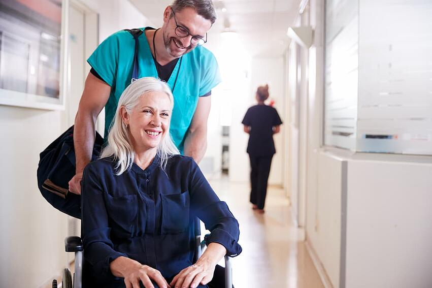 Orderly pushing patient in a wheelchair