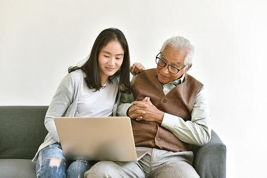 Daughter looking over laptop with elderly father