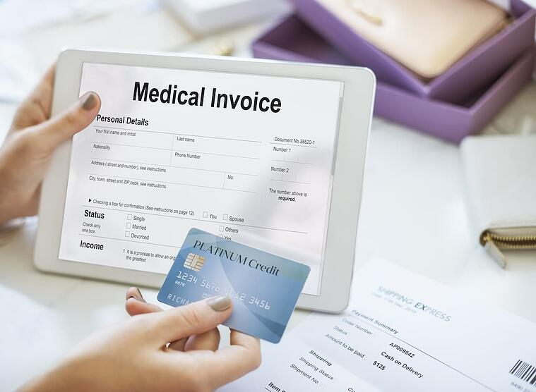Patient looking over medical invoice on a tablet while holding a credit card