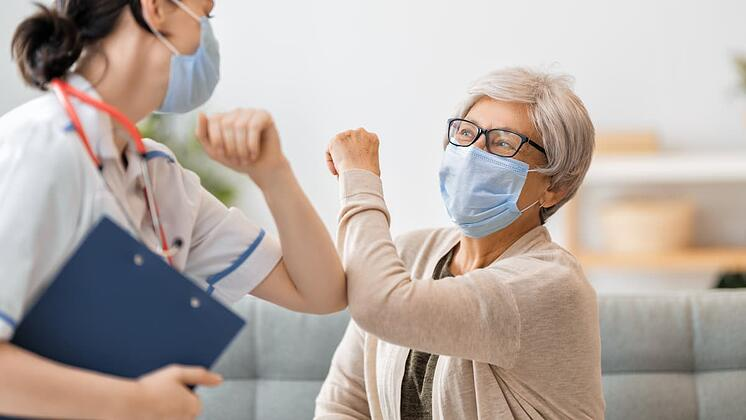 Older patient in a mask elbow bumping a nurse in a mask