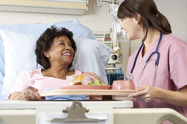 Patient accepting food tray from hospital nurse